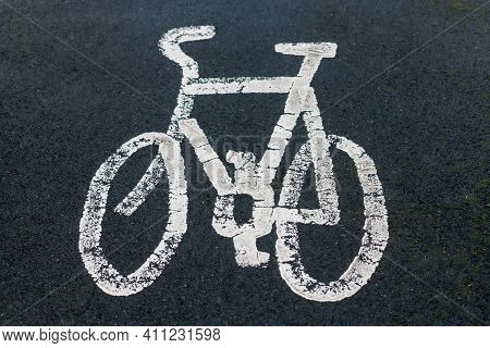 A Painted White Bicycle On Dark Black Tarmac Showing A Cycle Lane