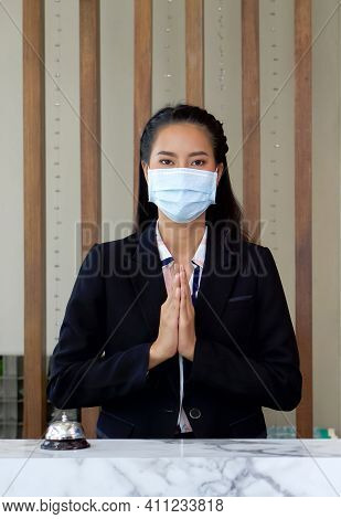 The Hotel Receptionist Raise Her Hand To Pay Respect In Thai Culture While Wearing A Surgical Mask.