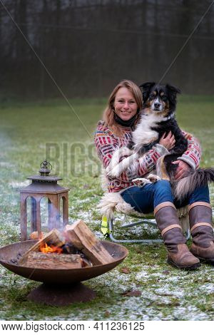 Blonde Woman With Her Australian Shepherd Dog On Her Lap. In Casual Thick Winter Sweater Outside On