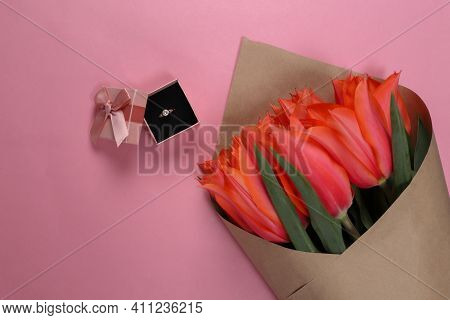 Ring With A Diamond In A Gift Box And A Bouquet Of Red Tulips On A Pink Background. Birthday, Valent