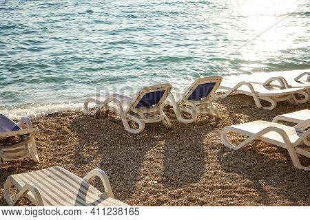 Vacation Concept: Pair Of Beach Loungers On The Deserted Coast Sea At Sunrise.