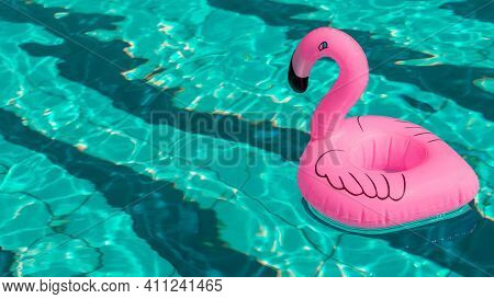 Summer Concept Background. Pink Inflatable Flamingo In Pool Water For Summer Beach Background. Pool