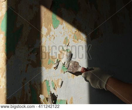 A Spatula In The Hand Of A Gloved Worker, Scrapping Scraps Of Old Wallpaper On The Wall Of The Room