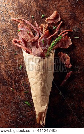Slices Of Spicy Dry-cured Meat With Rosemary In A Paper Bag On An Old Brown Background. Top View.