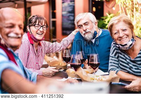 Happy Senior Friends Taking Selfie At Restaurant With Open Face Mask - Retired People Having Fun Tog