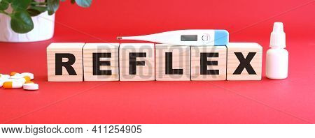 The Word Reflex Is Made Of Wooden Cubes On A Red Background With Medical Drugs.