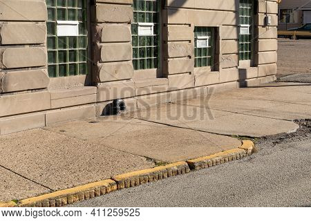Concrete Sidewalk And Asphalt Street Before A Building Of Large Dressed Stones, Windows Filled With