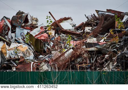 Metal Scrap Waste Dump For Recycling. City Fenced Landfill. Iron Garbage And Trash.