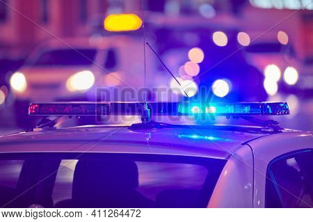 Police Car Lights At Night City Street. Red And Blue Lights. Road Traffic Accident. Evening Patrolli