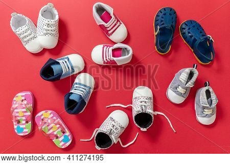 Baby Boy And Girl Shoes Variety On Red Color Background, Top View..