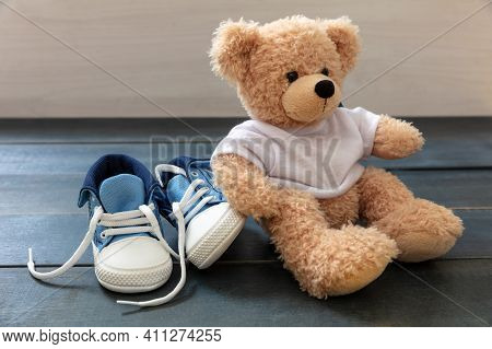 Baby Shoes And Teddy Bear On Blue Wooden Floor Background
