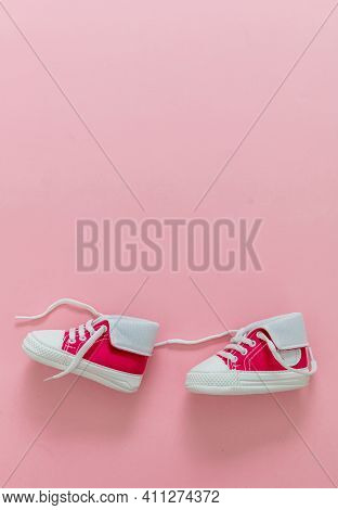 Baby Girl Shoes On Pastel Pink Color Background, Copy Space