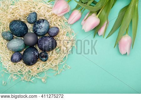 Bird's Nest With Blue Cosmic Eggs And Pink Tulip, Happy Easter Background. Top View, Copy Space
