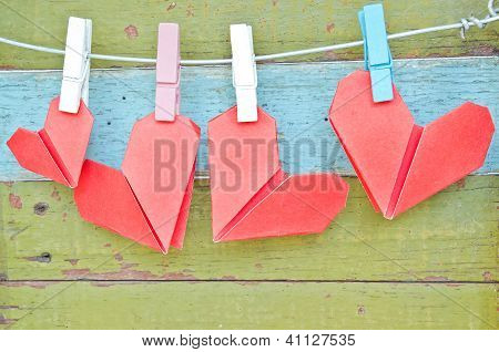 Paper Heart Hanging On The Clothesline. On Old Wood Background.