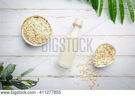 Vegan Non Dairy Oatmeal Milk In Bottles On White Wooden Background. Lactose Free Milk Substitute. To