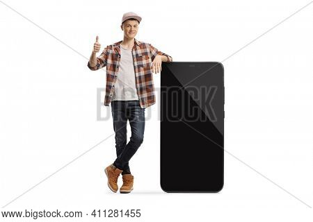 Full length portrait of a male teenager leaning on a big smartphone with blank screen and showing thumbs up isolated on white background
