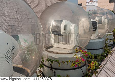 Kowloon, Hong Kong, China - May 13, 2010: Line Of White Robotic Light Canons Under Glass Sphere To W