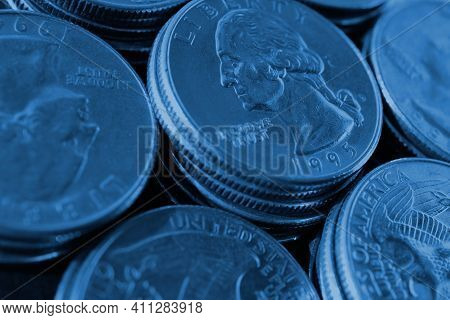 Piles Of Us American Coins Of 25 Cents Quarters Close-up. Dark Blue Tinted Background For News About