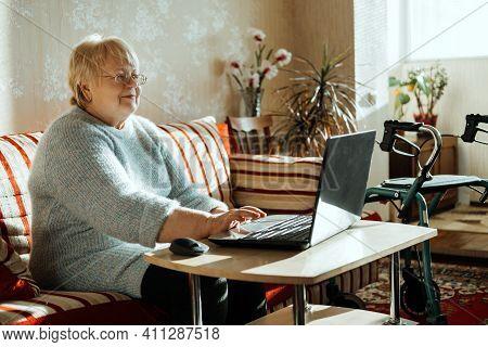 Senior Mature Candid Real Caucasian Woman Look At Laptop Screen At Home. Happy Senior Blonde Female