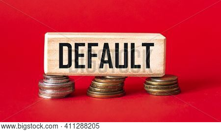 The Word Default Is Written On A Wooden Block That Stands On Coins And A Red Background. Debt Increa