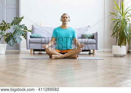 Photo Of A Middle Aged Man Practicing Yoga At Home. He Sits In The Lotus Position With Headphones An