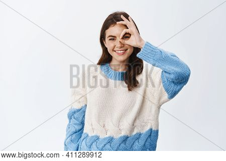 Young Positive Girl In Sweater, Showing Okay Sign, Making Alright Gesture Over Eye And Smiling, Stan