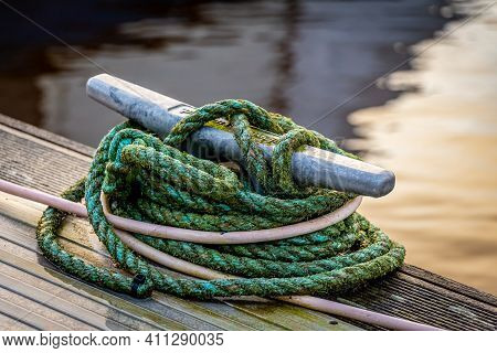 Rope Tied Around A Metal Bollard Mooring On A Wooden Jetty