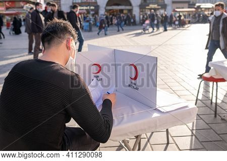 Eminonu, Istanbul, Turkey - 02.26.2021: A Male Blood Donation Volunteer Sits And Reads Permission Fo