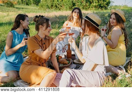 Friends Having Picnic In The Countryside. Group Of Young Women Sitting On Blanket In Park Near Trees