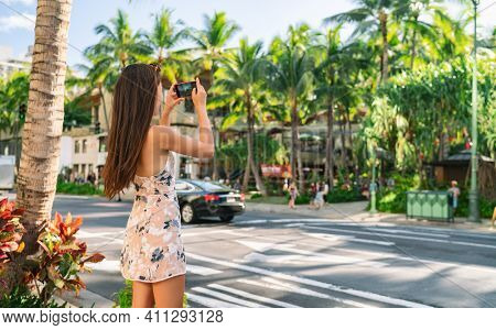 Honolulu city woman tourist taking pictures with phone camera walking on street in Waikiki, Oahu, Hawaii. USA summer travel.