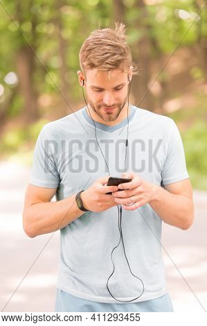 Pairing His Fitness Watch With His Smartphone. Sportsman Using Fitness Tracker For Training Outdoor.
