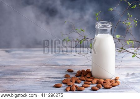 Almond Milk Bottle With Almonds On A White Wooden Background, Vegetarian Milk, Healthy Food Concept,