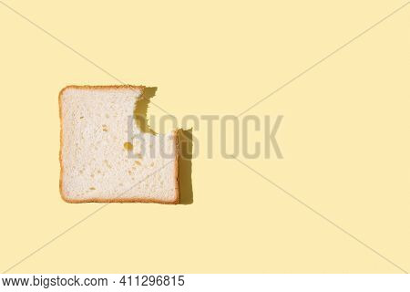 A Slice Of Bitten Bread On A Yellow Background In Bright Sunlight, A Slice Of Bread For Toast, Close