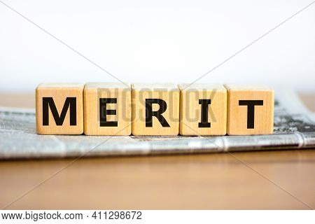 Merit Symbol. Wooden Cubes With The Word 'merit'. Beautiful White Background, Copy Space. Newspaper.
