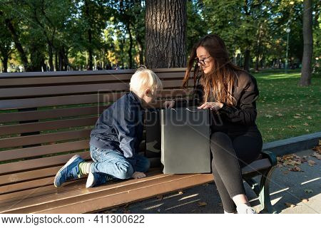 Child Boy And Nanny Are Sitting On Bench In Park And Look Into Shopping Bags.