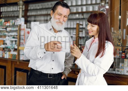 Professional Beautiful Female Woman Pharmacist Talking With Male Senior Client While Showing Him The