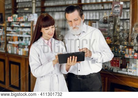 Pharmacy And Prescription Concept. Young Woman Pharmacist With Tablet, Reading Patients Prescription