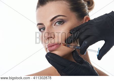 Young Attractive Woman Looks At Camera While Receiving An Injection On Lips By Aesthetician In Black
