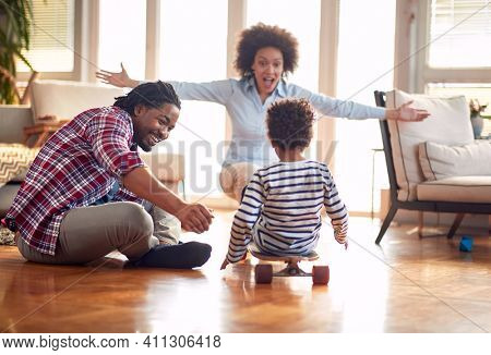 A happy parents playing with their son on the floor in a cheerful atmosphere at home. Family, together, love, playtime