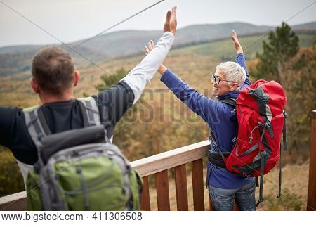 Happy hikers couple with raise arms looking landscape