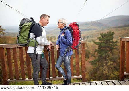 Senior hikers couple looking at each other at viewpoint