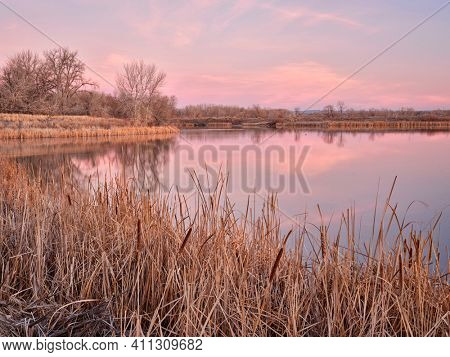 early spring dawn over a calm lake in one of natural areas along the Poudre River in Fort Collins, Colorado