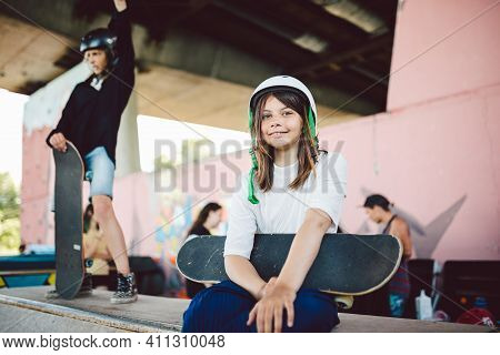 Beautiful Teenage Girl In White Helmet Sits With Skateboard In Her Hands On Pipe Ramp In An Extreme