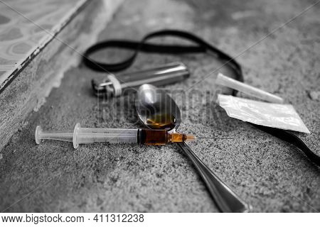 Amphetamine On Spoon And In Syringe With Black  Rubber Band On Dirty Dark Cement Floor. Addictive Su