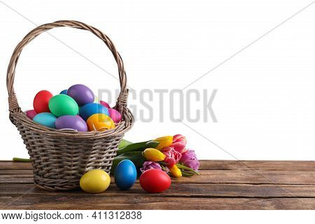 Colorful Easter Eggs In Wicker Basket And Tulips On Wooden Table Against White Background