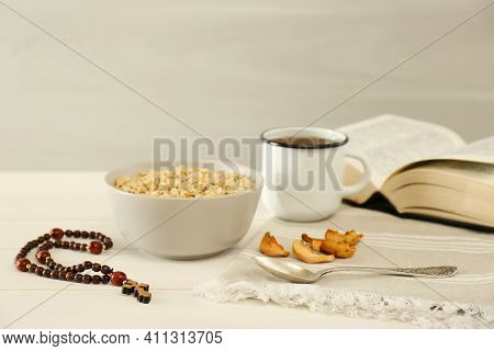Rosary Beads, Oatmeal Porridge, Dried Apples, Drink And Bible On White Wooden Table. Lent Season