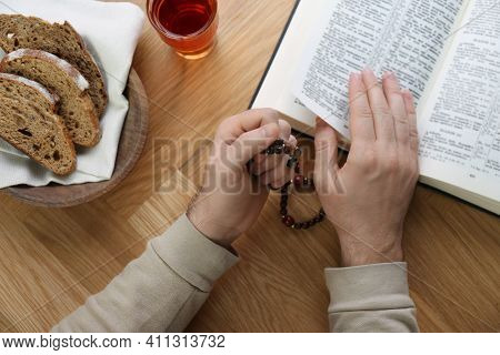 Man With Holy Bible, Prayer Beads, Bread And Drink At Wooden Table, Top View. Great Lent Season