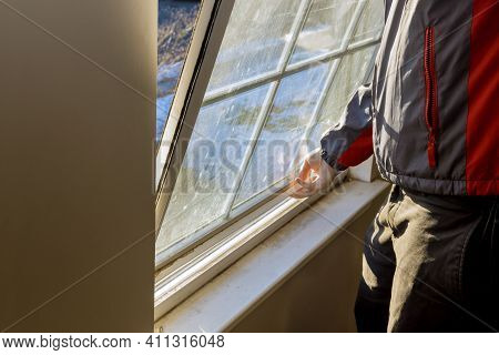 A Carpenter With Process Of Removing An Bring Down Window From An Opening In A House Before Replacin