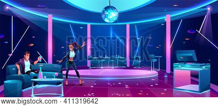 Young Couple At Night Club Party, Man Sitting On Couch Drinking Alcohol Cocktail, Woman Dancing In F