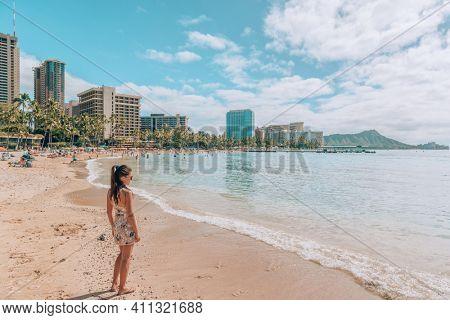 Waikiki beach travel lifestyle. Tourist woman walking in Honolulu, Hawaii during winter holidays. Summer vacation destination.